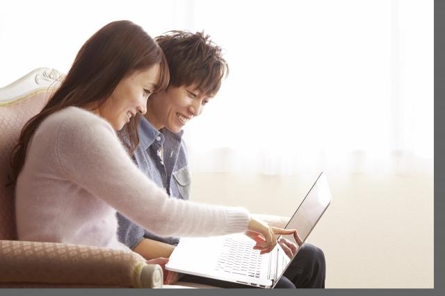 パソコンを見て笑うカップル