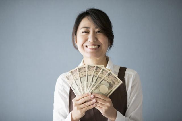 お金をもって喜んでいる女性い