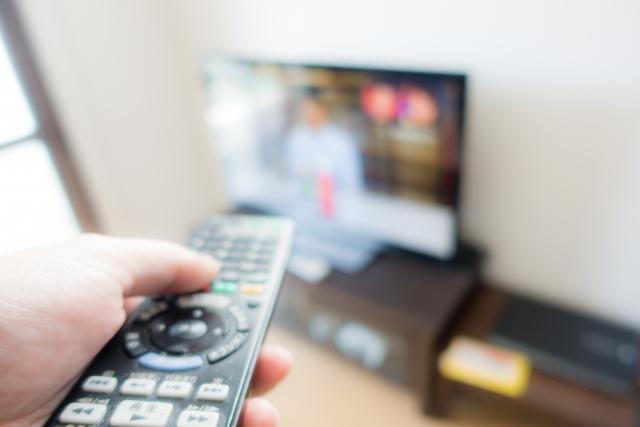 テレビのリモコンを操作する人